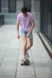 Adolescente elegante que monta un longboard Imágenes de archivo libres de regalías