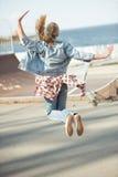 Adolescente elegante que salta en el parque del monopatín Fotografía de archivo