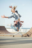 Adolescente elegante que salta en el parque del monopatín Imagenes de archivo