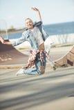 Adolescente elegante que salta en el parque del monopatín Fotos de archivo libres de regalías
