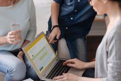 Adolescente elegante que señala en la pantalla del ordenador portátil Imágenes de archivo libres de regalías