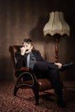 Adolescente elegante que se sienta en butaca Foto de archivo