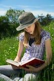 Adolescente elegante que se sienta en la hierba con las piernas cruzadas leyendo un libro al aire libre Fotografía de archivo libre de regalías