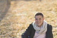 Adolescente elegante que se sienta en la tierra en llevar del parque de la ciudad ey Imagen de archivo
