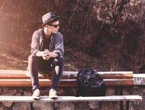 Adolescente elegante que se sienta en un banco de madera Imagen de archivo