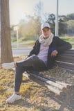 Adolescente elegante que se sienta en un banco de madera en un casu de la calle de la ciudad Imagen de archivo