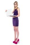 Adolescente elegante que sostiene el nuevo ordenador portátil Fotografía de archivo