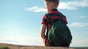 Adolescente em um t-shirt vermelho com uma trouxa no seu para trás, no por do sol, sentando-se em um monte alto, apreciando a nat vídeos de arquivo