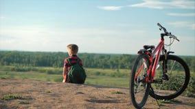 Adolescente em um t-shirt vermelho com uma trouxa em sua parte traseira, no por do sol, sentando-se em um monte alto, apreciando  filme