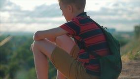 Adolescente em uma camisa vermelha com uma trouxa no seu para trás, no por do sol, sentando-se em um monte alto e olhando as nuve video estoque
