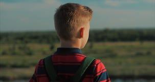 Adolescente em uma camisa vermelha com uma trouxa no seu para trás, no por do sol, sentando-se em um monte alto e olhando as nuve vídeos de arquivo