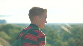 Adolescente em uma camisa vermelha com uma trouxa no seu para trás, no por do sol, sentando-se em um monte alto e olhando as nuve filme