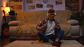 Adolescente emocionado en auriculares que escucha la música que finge a los tambores, pasión metrajes