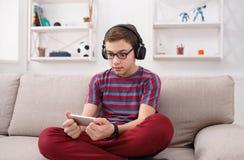 Adolescente emocionado que juega al juego móvil en casa Imagenes de archivo