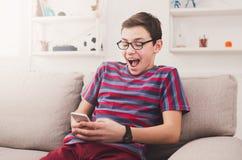 Adolescente emocionado que juega al juego móvil en casa Imágenes de archivo libres de regalías