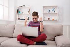Adolescente emocionado que juega al juego online en el ordenador portátil en casa Foto de archivo