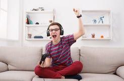 Adolescente emocionado que juega al videojuego en casa Imagen de archivo