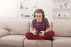 Adolescente emocionado que juega al videojuego en casa Fotos de archivo libres de regalías