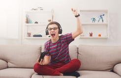 Adolescente emocionado que juega al videojuego en casa Foto de archivo libre de regalías