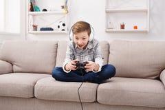 Adolescente emocionado que juega al videojuego en casa Fotografía de archivo libre de regalías