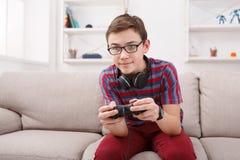Adolescente emocionado que juega al videojuego en casa Imágenes de archivo libres de regalías
