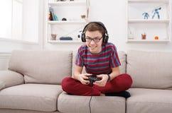 Adolescente emocionado que juega al videojuego en casa Imagenes de archivo
