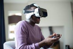 Adolescente emocionado que juega al videojuego en casa que lleva las auriculares de la realidad virtual imagenes de archivo