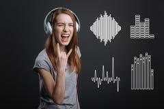Adolescente emocionado que muestra una muestra de la roca mientras que escucha la música en auriculares Imagenes de archivo