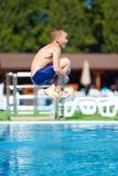 Adolescente emocionado que salta en piscina Fotos de archivo