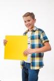 Adolescente emocional del muchacho en una camisa de tela escocesa con la hoja de papel amarilla para las notas Fotografía de archivo