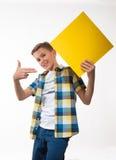 Adolescente emocional del muchacho en una camisa de tela escocesa con la hoja de papel amarilla para las notas Foto de archivo libre de regalías