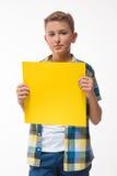 Adolescente emocional del muchacho en una camisa de tela escocesa con la hoja de papel amarilla para las notas Imágenes de archivo libres de regalías