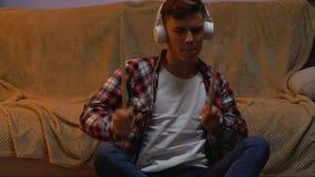Adolescente emocional en auriculares que escucha la música, aprendiendo cómo jugar los tambores almacen de metraje de vídeo