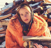 Adolescente en abrigo de pieles rojo con un poco de leña Imagen de archivo