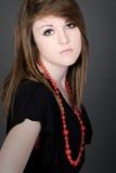 Adolescente en alineada negra y collar rojo del grano Imagen de archivo libre de regalías