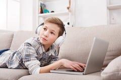 Adolescente en auriculares con el ordenador portátil en casa Fotografía de archivo