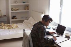 Adolescente en auriculares en el escritorio en el dormitorio, visión elevada Fotos de archivo libres de regalías