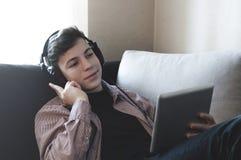 Adolescente en auriculares que escucha la música Fotografía de archivo libre de regalías