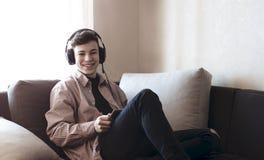 Adolescente en auriculares que escucha la música Imágenes de archivo libres de regalías