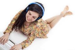 Adolescente en auriculares que escucha la música Foto de archivo