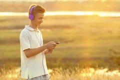 Adolescente en auriculares que escucha la música en la puesta del sol en el campo Foto de archivo