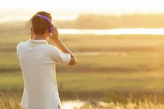 Adolescente en auriculares que escucha la música en la puesta del sol en el campo Imagen de archivo