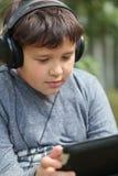 Adolescente en auriculares usando el cojín al aire libre Imagen de archivo