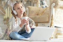Adolescente en auriculares usando el ordenador portátil Fotografía de archivo