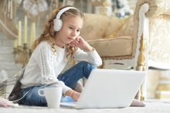 Adolescente en auriculares usando el ordenador portátil Imágenes de archivo libres de regalías