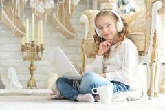 Adolescente en auriculares usando el ordenador portátil Fotos de archivo
