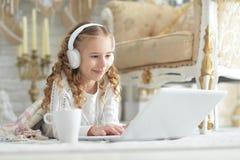 Adolescente en auriculares usando el ordenador portátil Imagenes de archivo