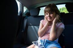 Adolescente en auriculares usando el teléfono móvil en el asiento trasero del coche Fotografía de archivo