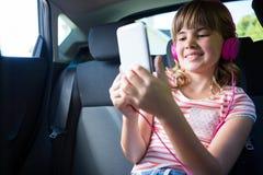 Adolescente en auriculares usando la tableta digital en el asiento trasero del coche Fotografía de archivo libre de regalías