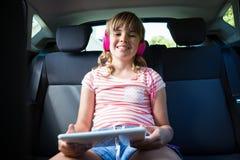 Adolescente en auriculares usando la tableta digital en el asiento trasero del coche Fotos de archivo